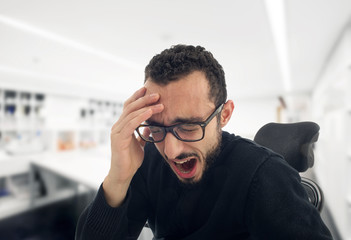 young businessman yawning at work in office..