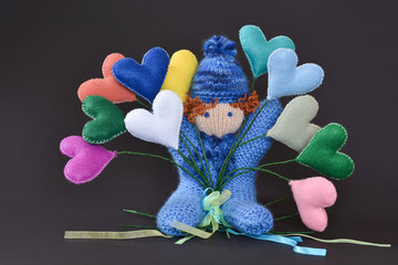 Handmade puppet boy playing with heart toys made by wool