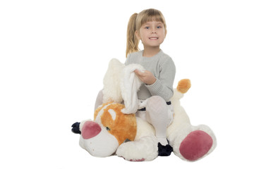 little girl sits on a toy dog