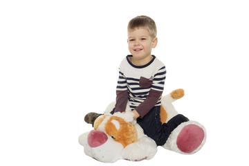 little boy sits on a toy dog
