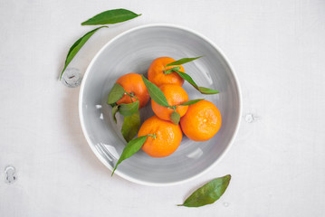 Tangerines with green leaves on white wooden background. Vertica