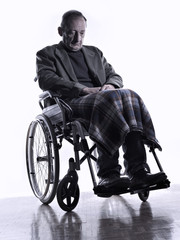 Man sitting on a wheelchair looking down