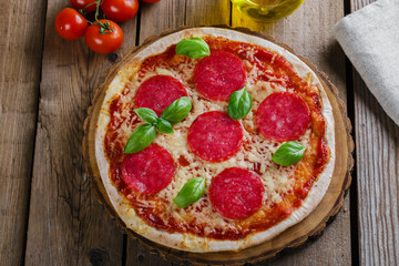 pizza with salami round on a wooden surface