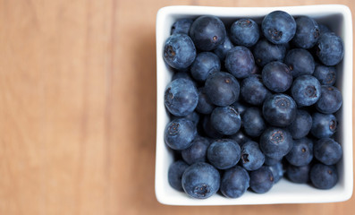 A white square bowl with ripe blueberries on a table