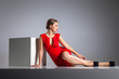 Beautiful blonde woman posing in red dress .