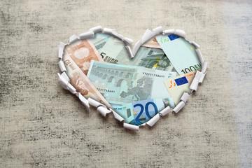Euro banknotes through torn gray paper