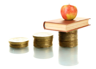Apple and book standing on stack of coins isolated on white