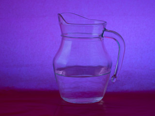 Glass jug with water on purple, mauve background.