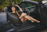 Portrait of a young lady in the car in a big black hat. - 77750327
