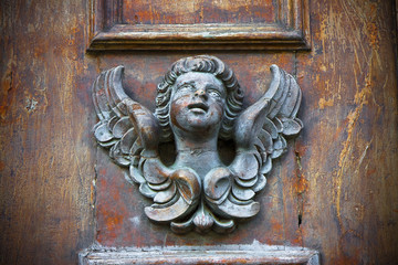 Sculpture of an angel on a wooden door in Italy