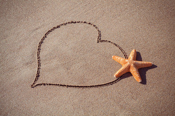 valentine's day concept at beach. big starfish on drawn heart.