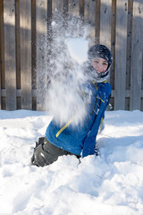 Child throwing a ball of snow
