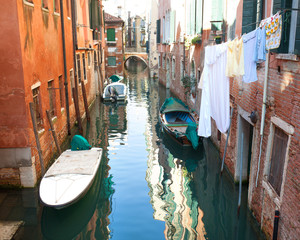 Venetian canal with boats and clothes hanging out to dry