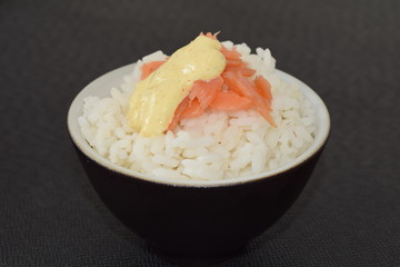 Sushi with salmon and sauce in a bowl on a black background.