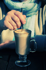 woman is holding cup of coffee cappuccino