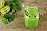 Healthy green smoothie with spinach and kiwi in a jar on wood
