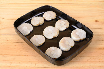 Fresh scallops in a black tray.