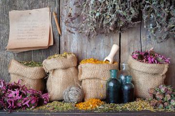 Healing herbs in hessian bags near wooden wall, herbal medicine.