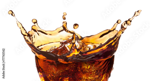 Splash from ice cubes in a glass of cola. - 77763562