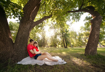 couple in love sitting under a big tree in the park