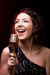 Attractive young woman vocalist singing with retro microphone