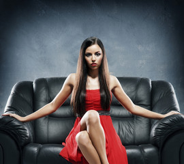 Young, beautiful and glamour woman in a red dress on a sofa