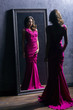 Young and gorgeous actress in a long dress near the mirror