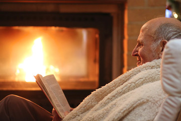 Senior woman relaxing at by fireplace