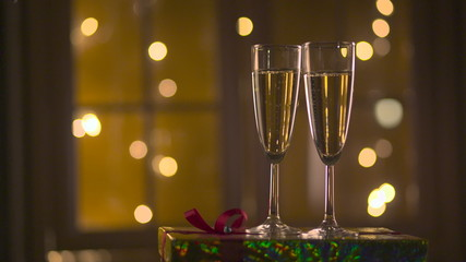 Champagne Pouring from the bottle. Two Flutes with Sparkling