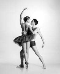 Couple of young and athletic ballet dancers on grey