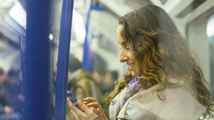 Attractive young woman using her phone on a train