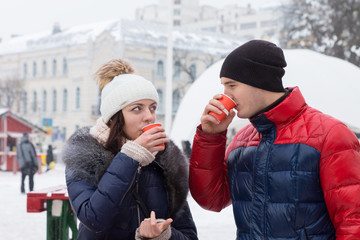Couple sipping hot drinks in a wintry town square