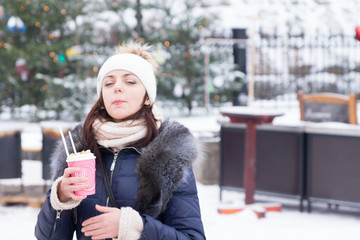 Young woman enjoying a hot drink in winter