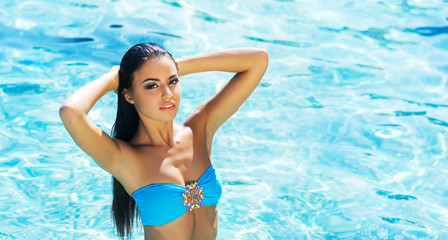 Beautiful, active and sporty girl swimming in a pool at summer