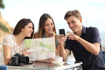 Group of tourist friends consulting gps map in a smart phone