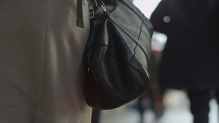 Woman's handbag on display as she walks in front of camera