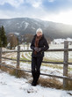 woman leaning against wooden fence on highland farm in Alps