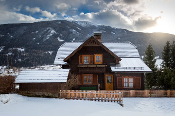 traditional wooden house in Alps covered with snow