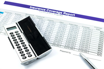 insurance coverage report with calculator and pen for business