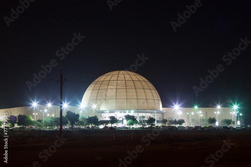 Dubai Outlet Mall illuminated at night. Dubai, UAE - 77779585