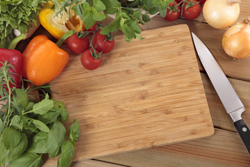 Herbs and vegetables with a blank chopping board. Space for copy