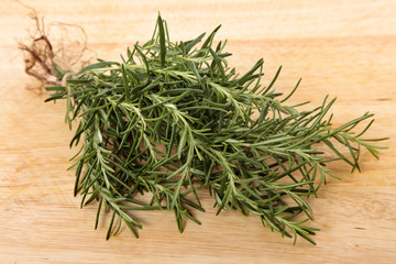 Bunch of fresh rosemary on an old wooden chopping board