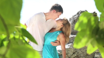 handsome man embrace and kiss blonde girl sitting on rock