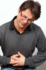 Mann, schmerzverzerrtes Gesicht, hält sich Bauch