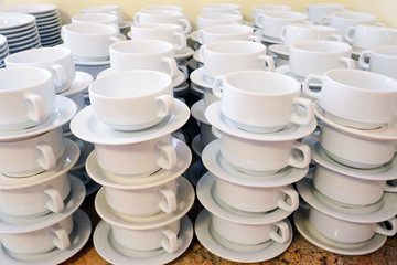 White cups for tea piled on table with plates for coffee break