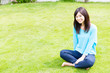 young asian woman relaxing on the lawn