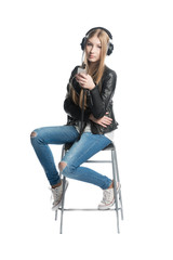 Isolated on white girl is listening music in wired headphones