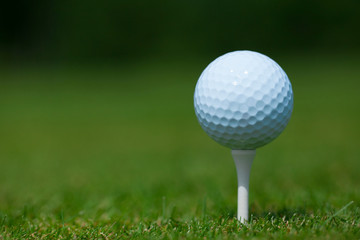 golf ball on a white tee with a green grass in background