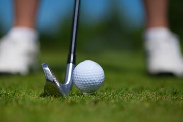 Golf ball on tee and golf club on golf course