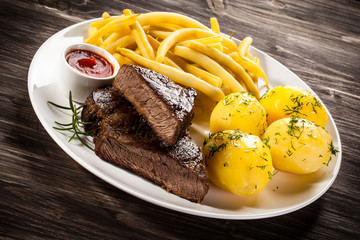 Beefsteaks, boiled potatoes and vegetables